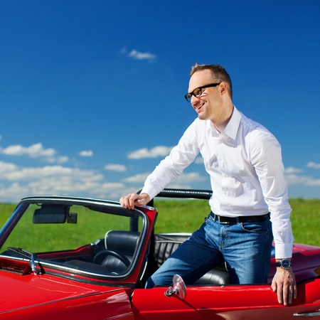 open car door: Young man standing in convertible car over the blue sky background Stock Photo