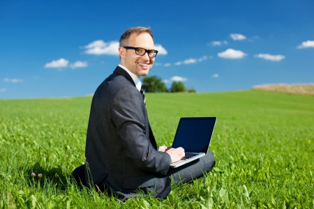field glass: Businessman working outdoors under a blue sky sitting in a green grassy field looking back at the camera with a cheerful smile