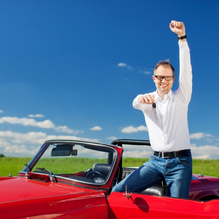 open car door: Excited man celebrating ownership of a cabriolet standing with the hood down and door open raising his arm in jubilation and holding out the key in sunny fresh countryside