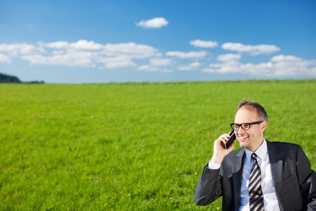 cellular phone call: Businessman talking on his mobile in nature standing in his suit in a beautiful open green grassy field under a sunny blue sky