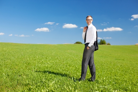 Businessman standing in a green meadow against the blue sky photo
