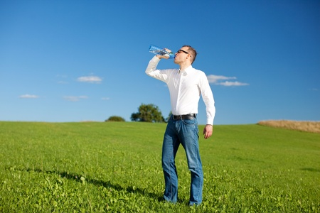 Man drinking mineral water quenching his thirst as he stands in a beautiful green field on a sunny day photo