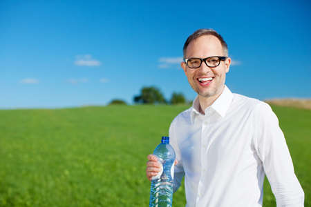 Smiling man drinking bottled water in a lush green field against a blue sky Reklamní fotografie