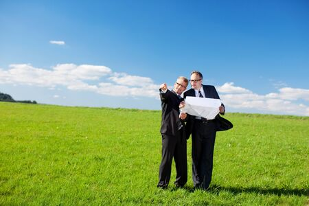 building site: Businessmen discussing a building plan or blueprint standing in the middle of a lush green field pointing to a possible site to locate the building