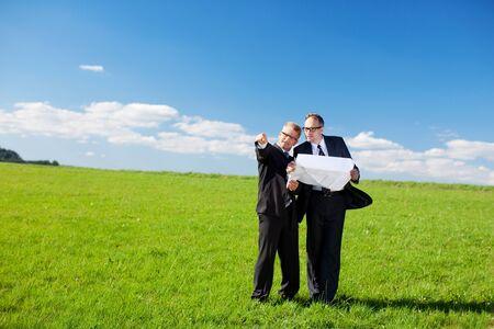 Ondernemers bespreken van een bouwplan of blauwdruk staande in het midden van een weelderig groen gebied wijzen op een mogelijke plaats om het gebouw te lokaliseren
