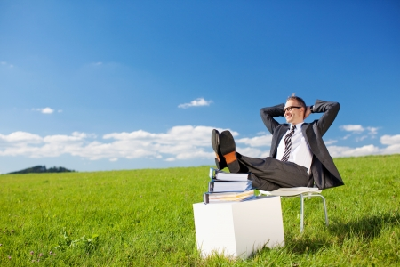 greenfield: Young businessman relaxing in Greenfield under the blue sky Stock Photo