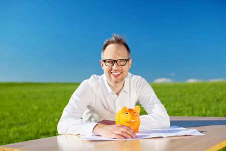 Happy businessman sitting with piggybank on his table outdoors photo