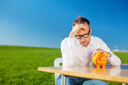 shortfall: Dejected man looking at his piggy bank with his head in his hand while seated at a table in a beautiful green spring field