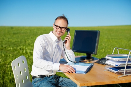 man using computer: Smiling businessman calling through telephone in office outdoors Stock Photo