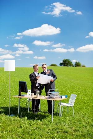 Dos arquitectos planean algo en prado verde