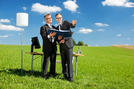 Two businessmen planning something in green meadow