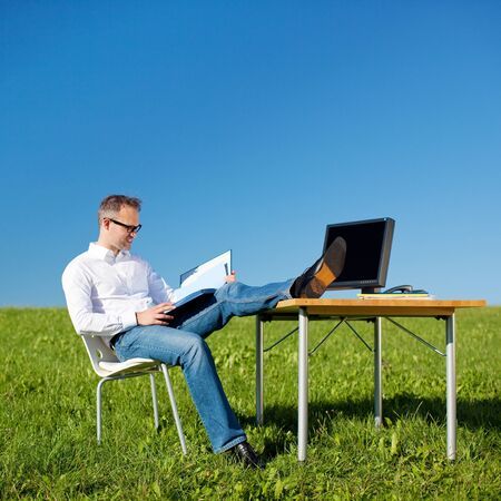 Relaxing businessman reading book in a green meadow photo