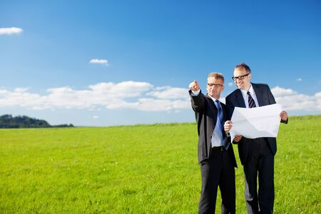 Businessman pointing and looking at something on green meadow photo