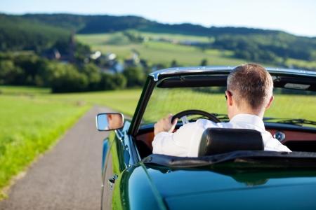 Rear view shot of man driving a convertible car outdoors photo