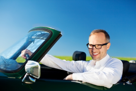 Happy man driving a convertible car over the blue sky background photo