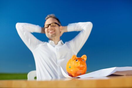 Conceptual portrait of happy businessman with piggybank on the table photo