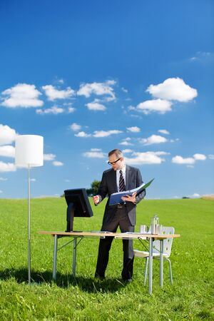 Businessman working with folder and computer on a green meadow Stock Photo