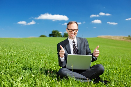 Successful businessman sitting cross legged in a grassy green field giving a thumbs up of approval for his beautiful outdoor office under a sunny blue sky photo