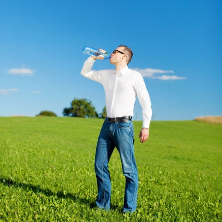 thirst quenching: Casual young man standing drinking bottled water in a green field under a blue sky quenching his thirst Stock Photo