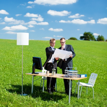 corporate meeting: Two businesspersons planning something in a green meadow Stock Photo