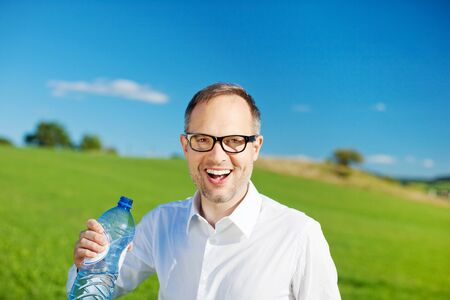 greenfield: Smiling man holding a bottled water over the Greenfield background Stock Photo