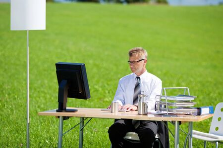 working space: Businessman sitting and working with computer outdoors Stock Photo
