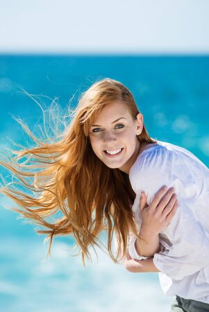 auburn hair: Windswept beautiful woman at the sea with her auburn hair flying in the breeze smiling at the camera