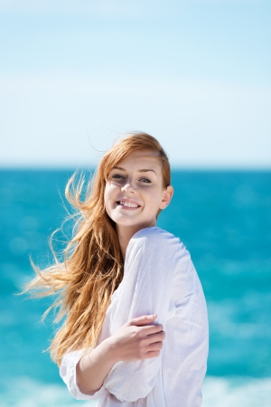 breeze: Beautiful young woman at the ocean standing against a turquoise blue sea with her hair blowing in the breeze