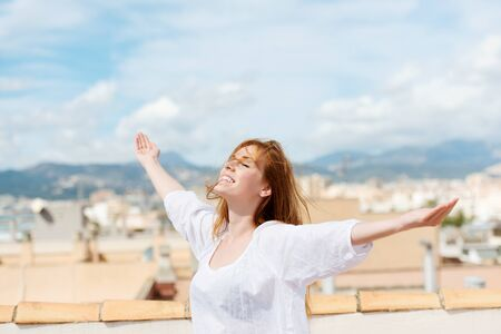 tilted: Woman on a rooftop embracing the sunshine standing with her arms outspread and her face tilted to the sun Stock Photo
