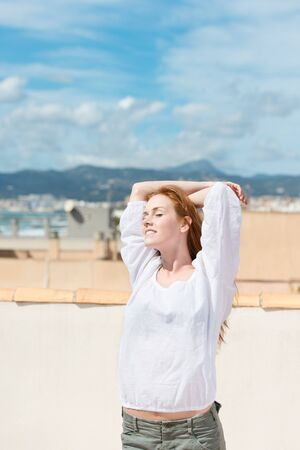 above head: Woman enjoying the sun above the town standing on a rooftop terrace with her arms raised above her head Stock Photo