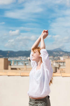arms above head: Young woman on a rooftop terrace enjoying the summer sunshine and raising her arms above her head Stock Photo