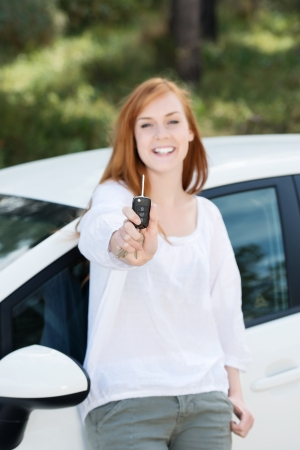 Laughing woman leaning back against her new car showing off a car key photo