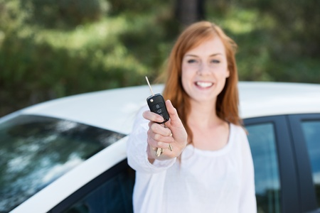 Happy young woman showing her car key outdoors photo