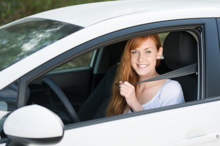 putting in: Beautiful young woman putting her seatbelt in the car