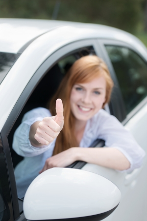 Happy woman in a new car leaning out of the window giving a thumbs up of approval and success photo