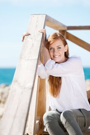 Woman enjoying the coastal sunshine sitting on a flight of wooden steps smiling at the camera with an ocean backdrop photo