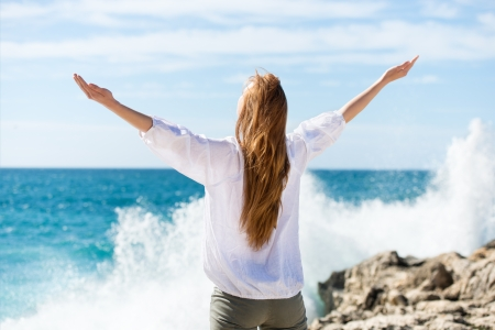 arms raised: Woman meditating at the sea standing with her arms outspread facing away from the camera towards the ocean on a beautiful sunny day
