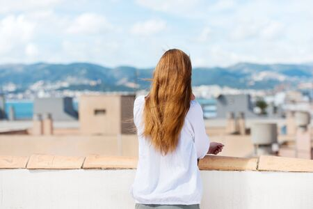 hair back: Woman standing on a roof terrace with her back to the camera looking out over a coastal town with shallow dof Stock Photo
