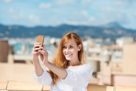 casuals: Smiling woman taking her photograph using a mobile phone and smiling as she poses for the picture