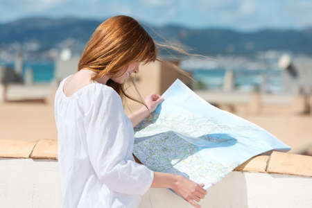 Woman consulting a map on an urban rooftop in the summer sunshine photo