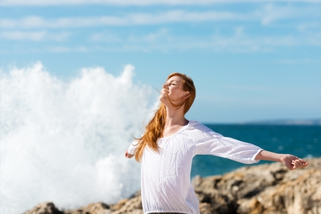 outspread: Beautiful young woman enjoying a healthy lifestyle at the sea standing with her arms outspread and head tilted to the sun against the spray of breaking waves Stock Photo