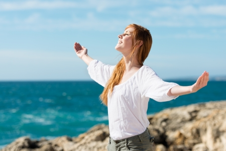 auburn hair: A pretty happy young woman enjoying the sun stands with her arms outspread against an ocean backdrop