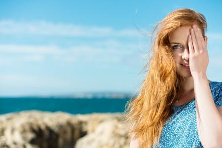 Pretty young redhead woman covering one eye with her hand as she stands on a rocky seashore photo