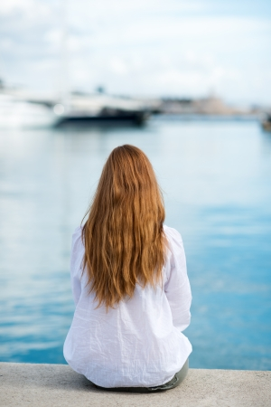 Woman sitting at the harbour on the quay with her back to the camera looking out at the moored boats, shallow dof photo