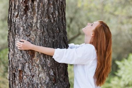 Mooie vrouw toont haar liefde voor de natuur met haar armen rond de stam van een boom opzoeken in de luifel met een mooie glimlach Stockfoto