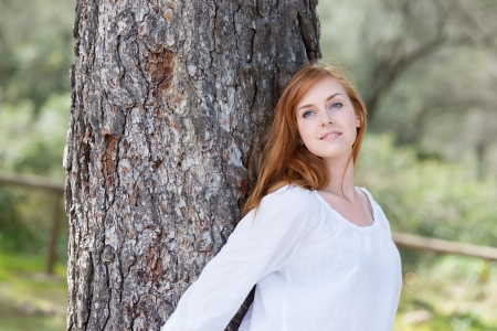 Conceptual portrait of fresh female leaning at the big trunk photo