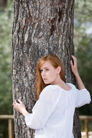 Portrait of cheerful woman posing with a big tree trunk photo
