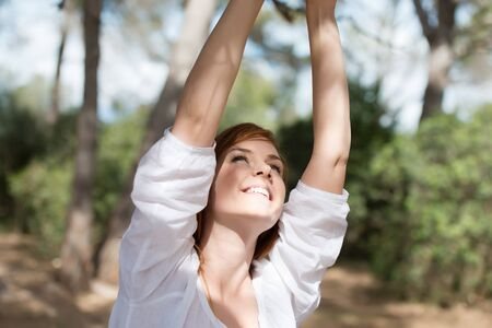 Smiling woman outdoors in woodland looking up at her raised hands which are off screen photo