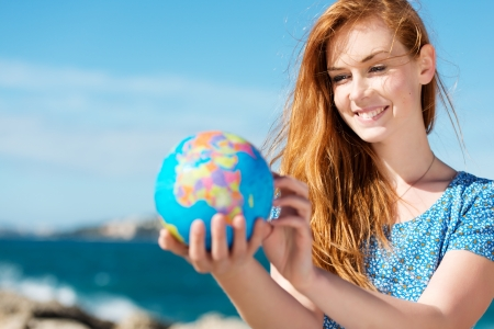 fair skin: Smiling beautiful young woman standing in the summer sunshine holding a globe at the sea with copyspace