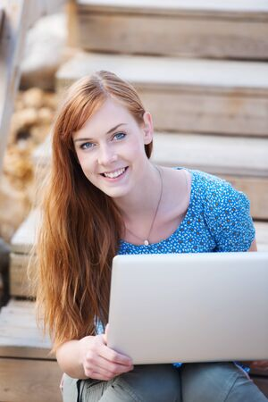 beautiful redhead: Smiling young redhead woman working outdoors on a laptop saitting on a flight of wooden stairs